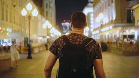 O pessoa anda na rua da volta do close up da cidade da noite para olhar a câmera e os sorrisos filme