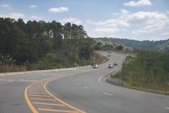 O pessoa conduz carros na estrada grande da curva entre montanhas ao curso imagem de stock