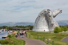 O pessoa que anda em torno do cavalo estrutura Kelpies no parque Falkirk da hélice Imagem de Stock Royalty Free