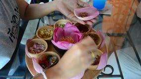 O pessoa tailandês asiático que cozinha o petisco tailandês tradicional chamado Miang Kham está envolvendo com as folhas vermelha filme
