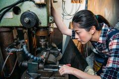 O pessoal fêmea da fábrica ajusta máquinas industriais Fotos de Stock Royalty Free