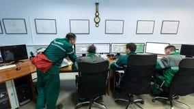 O pessoal senta-se no processamento do óleo dos controles de computadores vídeos de arquivo