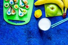 O petisco de Fuit para clildren Sanduíches, frutos e leite engraçados no copyspace azul da opinião superior do fundo da tabela Fotografia de Stock Royalty Free
