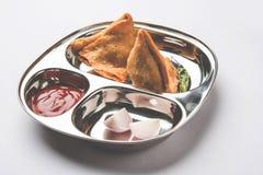 O petisco indiano Samosa do alimento serviu em uma placa de aço inoxidável com ketchup de tomate Fotos de Stock Royalty Free