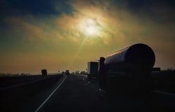 O petroleiro da gasolina monta a estrada nos raios do sol da noite Imagens de Stock Royalty Free