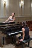 O pianista da mulher senta-se no piano e no cantor bonito Fotografia de Stock