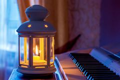 O piano na sala perto da janela é iluminado por um lamp_ da luz de vela fotografia de stock royalty free
