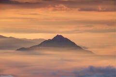 O pico cônico emerge do mar das nuvens e da névoa alaranjada no alvorecer fotos de stock royalty free