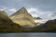 O pico de montanha afiado destacado pelo sol contra um céu tormentoso, uma geleira, uns montes gramíneos que aumentam acima do  imagem de stock