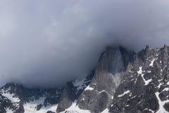 O pico na montanha é coberto com as nuvens chuvosas Imagens de Stock