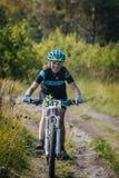 O piloto da menina na bicicleta monta na fuga Fotografia de Stock