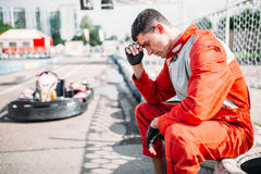 O piloto de Karting senta-se em um pneu, trilha exterior do kart Fotos de Stock Royalty Free