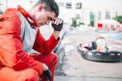 O piloto de Karting senta-se em um pneu, trilha exterior do kart imagem de stock