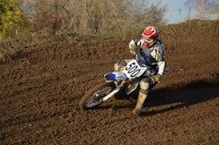 O piloto do motocross gira sobre uma inclinação de montanha imagem de stock royalty free
