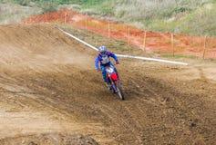 O piloto em uma motocicleta participa em motocross da raça, vai na areia Fotografia de Stock