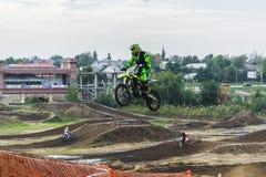 O piloto em uma motocicleta participa em uma raça do motocross, salta em um trampolim fotos de stock royalty free