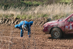 O piloto examina o carro dos danos Fotografia de Stock