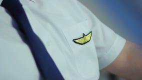 O piloto profissional vestiu-se no uniforme bonito que senta-se na cabina do piloto, fixando o laço filme