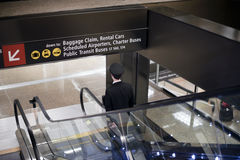 O piloto vai para baixo com a mala de viagem na escada rolante do aeroporto Foto de Stock