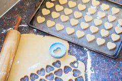 O pino do rolo de madeira, a massa crua e o coração deram forma ao cortador da cookie fotografia de stock
