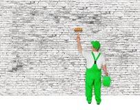 O pintor cobre a parede de tijolo branca Foto de Stock Royalty Free