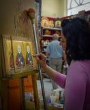 O pintor da mulher pinta ícones na loja do ícone fotografia de stock royalty free