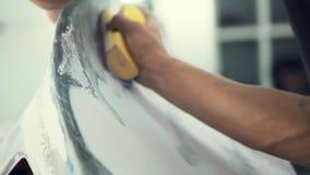 O pintor de casa lustra manualmente a superfície do carro video estoque