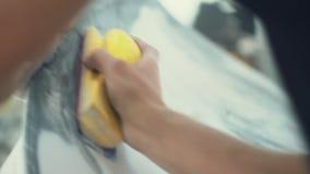 O pintor de casa lustra manualmente a superfície do carro filme