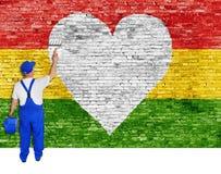 O pintor de casa pinta o símbolo do coração e a bandeira da reggae Imagens de Stock