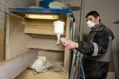 O pintor do carpinteiro pinta a placa da mobília com uma arma de pulverizador sobre Fotos de Stock Royalty Free