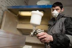 O pintor do carpinteiro pinta a placa da mobília com uma arma de pulverizador sobre Imagem de Stock Royalty Free