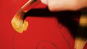 O pintor do close up faz a ouro fantástico testes padrões étnicos no vermelho video estoque