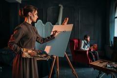 O pintor fêmea pinta o retrato do homem no estúdio da arte Imagens de Stock Royalty Free