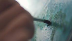O pintor faz um curso da escova na imagem escova de pintura do close up filme