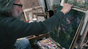 O pintor idoso pinta uma imagem na lona filme