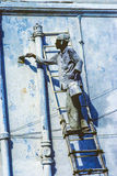 O pintor local pinta a parede velha na cor azul típica Fotografia de Stock