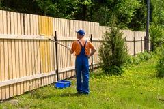 O pintor masculino trabalha na cerca de madeira Imagem de Stock