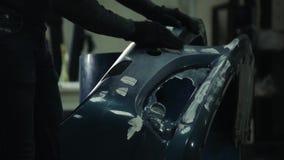 O pintor pinta um carro abundante na oficina de reparações video estoque