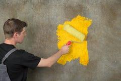 O pintor repinta uma parede estruturada no amarelo com um rolo da cor Foto de Stock