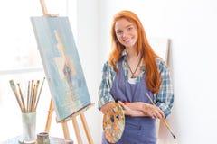 O pintor satisfeito feliz da mulher terminou pintar a imagem no estúdio da arte Imagens de Stock Royalty Free