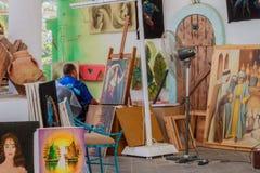 O pintor tira o assento em seu local de trabalho Imagens de Stock Royalty Free