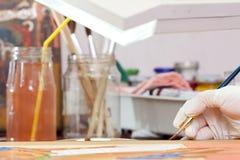O pintor trabalha no ícone novo com escova Foto de Stock