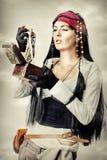 O pirata da mulher abre a caixa de tesouro Fotos de Stock
