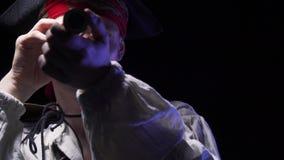 O pirata novo considerável com o chapéu armado em sua cabeça está olhando através de um telescópio pequeno dourado, 4k vídeos de arquivo