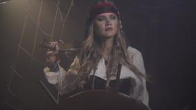 O pirata que fêmea o capitão está estando antes do volante, vento está fundindo, 4k vídeos de arquivo