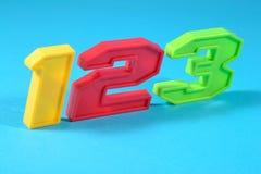 O plástico colorido numera 123 em um fundo azul Imagens de Stock Royalty Free