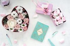 O plano bonito coloca na tabela branca Cores pastel, marshmallows, flores, pena de fonte, bloco de notas, rímel, perfume imagens de stock