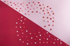 O plano bonito coloca o teste padrão dos corações com cópia-espaço no quartzo cor-de-rosa e fundo vermelho para o dia do ` s do V Fotos de Stock