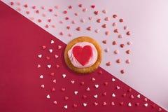O plano bonito coloca o teste padrão dos corações com queques com creme e um coração vermelho Fotos de Stock