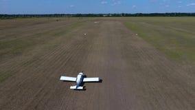 O plano branco do espanador da colheita decola em um campo contra um fundo do céu azul, tiro aero Movimento lento filme